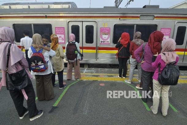 Sejumlah penumpang berdiri di garis antrean penumpang saat menunggu KRL di Stasiun Juanda, Jakarta, Selasa (8/8).