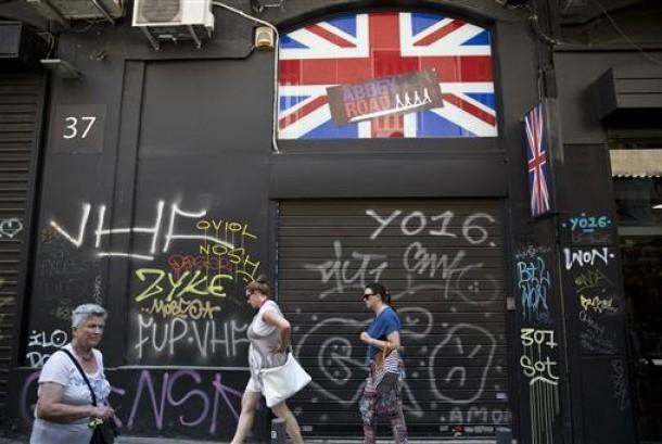 Sejumlah perempuan berjalan melewati sebuah toko memasang bendera Inggris di Athena, Yunani, 24 Juni 2016.