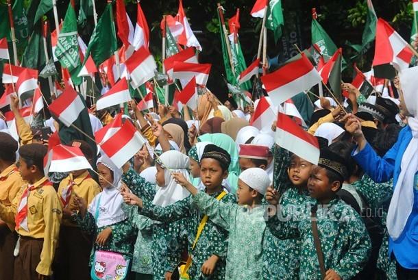 Sejumlah peserta mengibarkan bendera saat mengikuti upacara peringatan Hari Santri di Klaten, Jawa Tengah, Sabtu (22/10). Peringatan Hari Santri di Klaten diselenggarakan dengan mengusung tema Revolusi Jihat NU Merajut Kebhinekaan dan Kedaulatan Bangsa