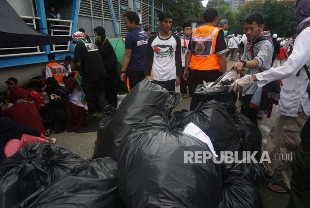 Sejumlah relawan dari komunitas pendaki muslim menata sampah yang telah mereka kumpulkan pada aksi bela Palestina di Monas,Jakarta, Ahad (17/12)