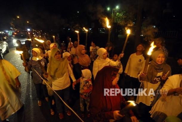 Sejumlah warga Kelurahan Taman sari berjalan membawa obor saat malam 1 Muharam di Jalan Ganesha, Kota Bandung, Sabtu (1/10) malam.
