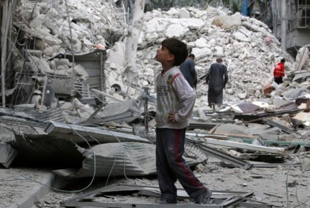 Seorang anak menyaksikan bangunan bekas pengeboman di Aleppo, Suriah.