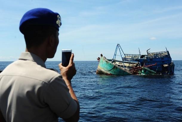 Seorang anggota Polisi Air (Polair) memotret dua kapal motor nelayan Vietnam yang ditenggelamkan di Pulau Datuk, Kabupaten Mempawah, Kalbar, Selasa (5/4). (Antara/Jessica Wuysang)