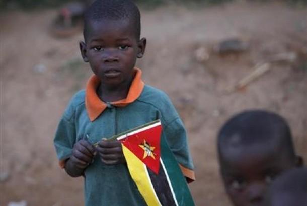 Seorang bocah memegang bendera Mozambik di pinggiran ibu kota Maputo.