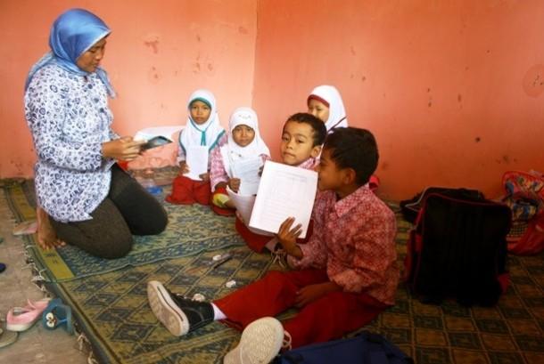 Seorang guru mengajar siswa kelas 2 yang hanya berjumlah lima murid di lantai SDN V Krasak, kec. Jatibarang, Kab. Indramayu, Jabar, Kamis (17/11). Akibat ruang kelas rusak siswa SDN V Krasak terpaksa belajar di rumah huni guru yang terletak di samping bang