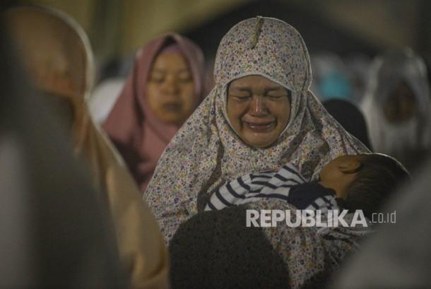 Seorang ibu yang menggendong anaknya menangis saat melakukan Shalat Subuh Berjamaah di Masjid Pusat Dakwah Islam (Pusdai) Kota Bandung, Jawa Barat, Senin (12/12).