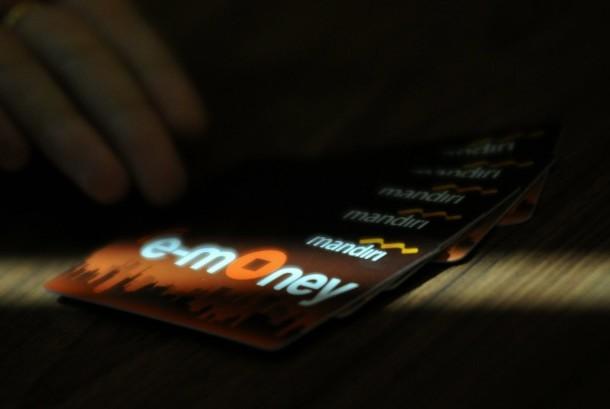 Seorang pegawai menunjukkan model layanan uang elektronik (E-Money) (Ilustrasi)