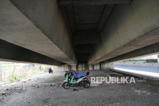 Seorang pengemudi ojek online beristirahat untuk melepas kantuknya di kolong flyover Pramuka Jakarta, Ahad (3/9).