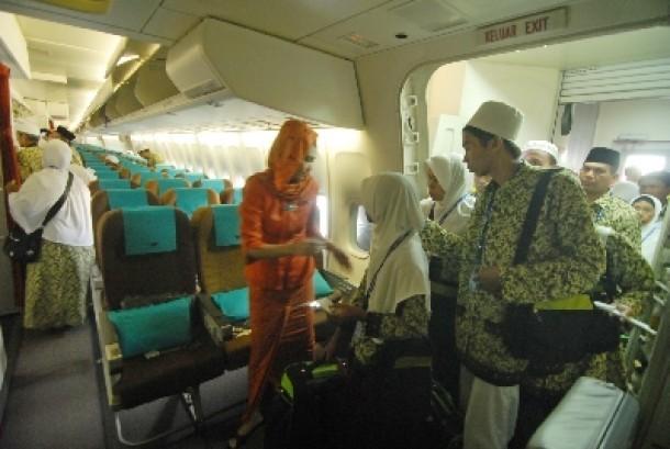 Seorang pramugari membimbing para calon jamaah umrah di kabin pesawat dalam penerbangan langsung menuju Jeddah.