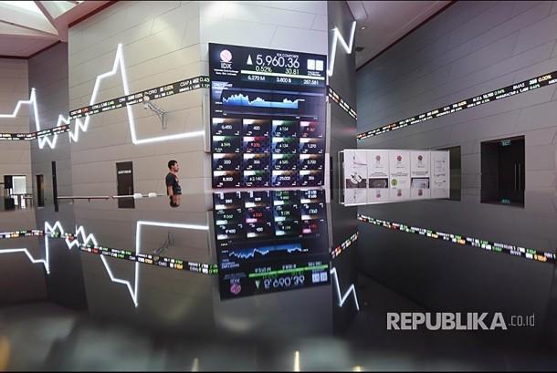 Seorang pria melintas di sekitar papan elektronik pergerakan saham di Bursa Efek Indonesia, Jakarta, Senin (23/10). Pada perdagangan Senin (23/10) kapitalisasi pasar BEI berhasil mencatatkan rekor tertingginya, yaitu sebesar Rp6.602,7 triliun.