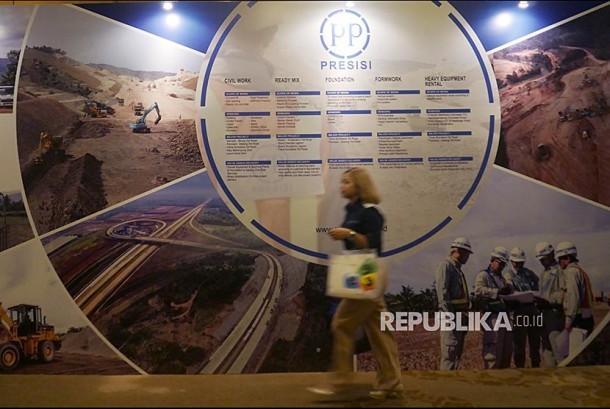 Seorang pengunjung melintasi banner Public Expose PT PP Presisi Tbk di Jakarta, Senin (23/10). Perusahaan konstruksi spesialis berbasis peralatan berat anak perusahaan PT PP (Persero) Tbk, mengumumkan rencana untuk melepaskan saham sebanyak-banyaknya 4.239.300.000 lembar saham (semua saham baru) dengan nilai nominal Rp100 per lembar.