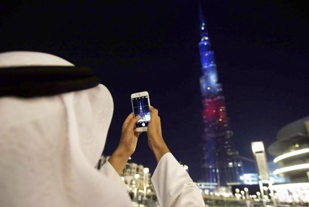 Seorang pria mengambil foto bangunan ikonik Dubai Burj Khalifa.