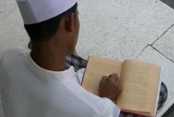 Seorang santri tengah membaca kitab kuning
