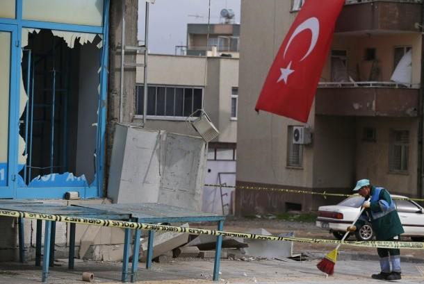 Seorang warga membersihkan pecahan kaca setelah serangan roket di Kota Kilis, Turki, Ahad (21/1).