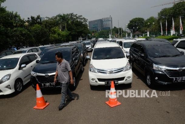 Sopir kendaraan sewa berbasis transportasi online menunggu saat uji KIR khusus di Silang Monas, Jakarta, Senin (15/8). (Republika/ Yasin Habibi)