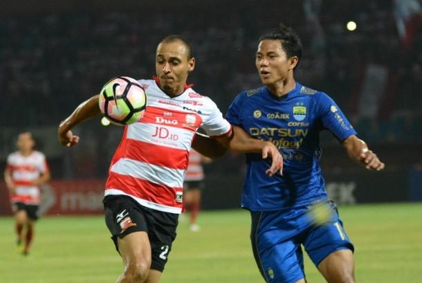 Striker Madura United (MU) Peter Osase Odemwingie (kiri) berusaha melewati bek Persib Bandung Ahmad Jufrianto (kanan) saat pertandingan Liga 1 di Stadion Gelora Ratu Pamelingan (SGRP) Pamekasan, Jawa Timur, Ahad (9/7).
