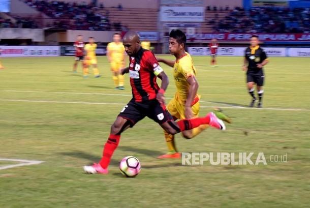 Striker Persipura Boaz Solossa berusaha melewati pemain belakang Bhayangkara FC dalam laga lanjutan Liga 1 Gojek Traveloka 2017, di stadion Mandala Jayapura, Papua, Jumat (12/5). Persipura berhasil raih tiga poin atas kemenangan terhadap Bhayangkara FC dengan skor 3-2.