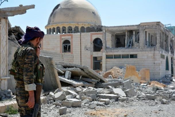Tentara berpatroli di sebelah bangunan yang hancur di Kota Raqqa, Suriah, 11 Juni 2017.