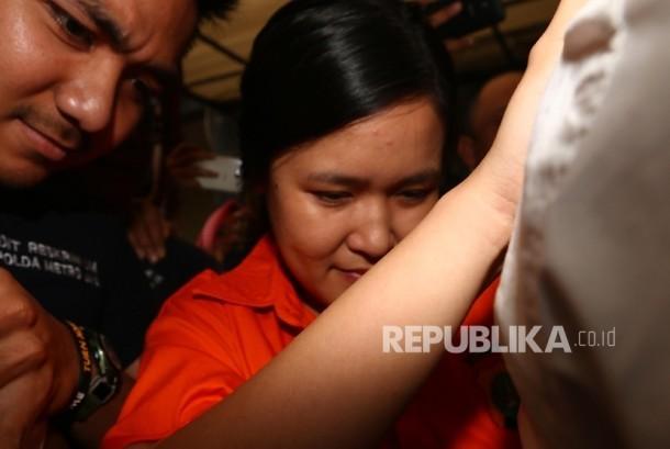 Tersangka kasus pembunuhan Wayan Mirna Salihin, Jessica Kumala Wongso dengan mengenakan baju tahanan dikawal petugas menuju ruang tahanan usai menjalani pemeriksaan selama 7 jam di gedung Direktorat Reserse Kriminal Umum Polda Metro Jaya, Jakarta, Senin (1