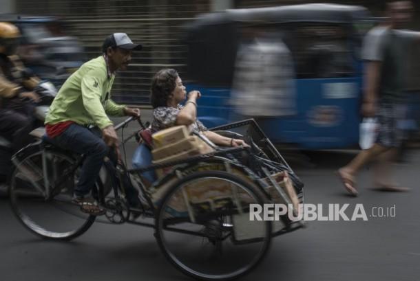 Tukang becak mengangkut penumpang saat melintas di kawasan Petak Sembilan, Glodok, Jakarta, Selasa (16/1).