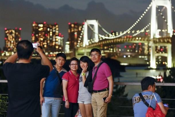 Turis berfoto dengan latar Jembatan Pelangi di Daiba Marine Park, Tokyo, Jepang.