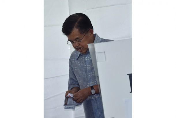Wakil Presiden Jusuf Kalla berada di bilik suara ketika memberikan hak suara pada Pilkada DKI Jakarta di TPS 3 Pulo, Kebayoran Baru, Jakarta, Rabu (15/2).