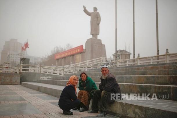 Warg aetnis Uighur dengan latar patung mendiang pemimpin China Mao Zedong di  Khasgar, Daerah Otonomi Xinjiang Uighur, China.