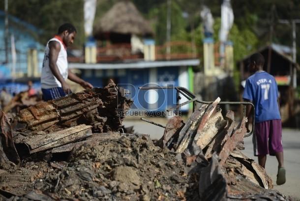 Warga beraktivitas di lokasi terbakarnya kios dan mushalla di Tolikara, Papua, Kamis (23/7).