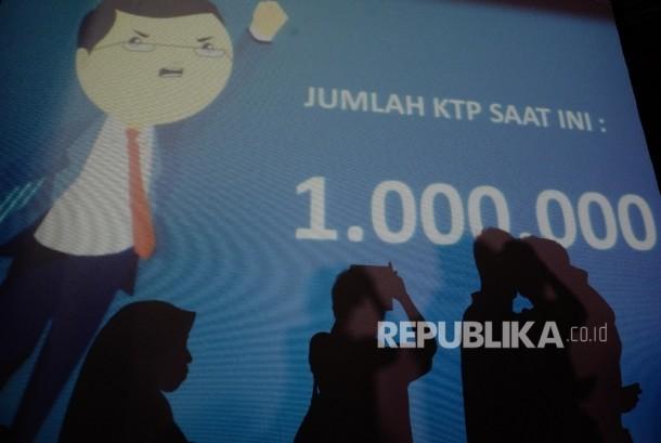 Warga berfoto di depan layar bertuliskan jumlah dukungan KTP sebanyak 1 juta di Sekretariat Teman Ahok, Jakarta, Ahad (19/6).