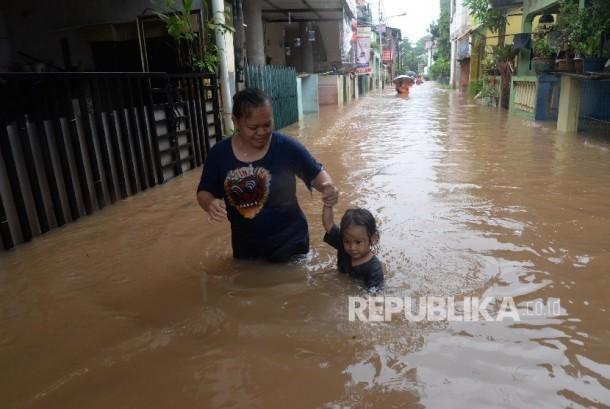 Warga berjalan menembus banjir di Kelurahan Cipinang Melayu, Kecamatan Makassar, Jakarta Timur, Senin (20/2).