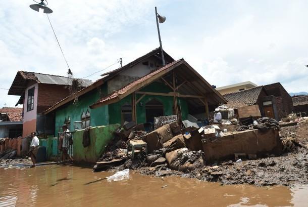 Warga berjalan seusai melaksanakan Salat Jumat di Masjid Al Mukmin yang berada di lokasi bencana banjir bandang aliran Sungai Cimanuk, Kampung Cimacan, Tarogong, Kabupaten Garut, Jawa Barat, Jumat (23/9).