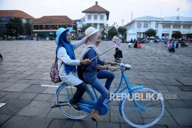 Warga bersepeda menikmati sore sambil menunggu waktu berbuka puasa di pelataran Gedung Fatahilah, Jakarta, Rabu (14/6).