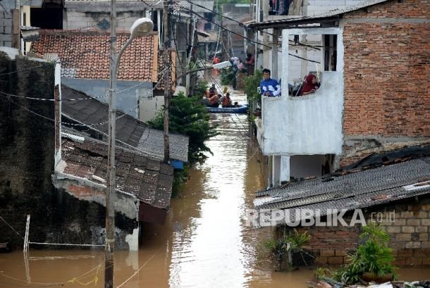 Warga bertahan dirumahnya ketika banjir di Kelurahan Cipinang Melayu, Kecamatan Makassar, Jakarta, Selasa (21/2).