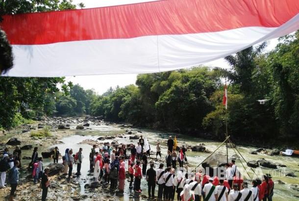 Warga dan sejumlah komunitas di Kota Sukabumi menggelar upacara hari kemerdekaan dan membentangkan bendera merah putih sepanjang 72 meter di pinggir Sungai Cimandiri, Kecamatan Lembursitu, Rabu (17/8).