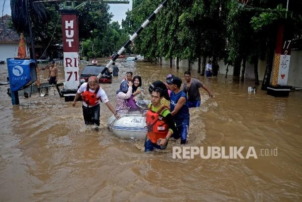 Warga dengan menggunkan perahu karet melintasi banjir akibat luapan Sungai Ciliwung, Bukit Duri, Jakarta, Kamis (16/2).