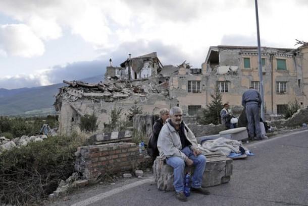 Warga Italia duduk di tepi jalan. Gedung yang hancur di Amatrice, Italia terlihat di belakangnya, Rabu, 24 Agustus 2016.