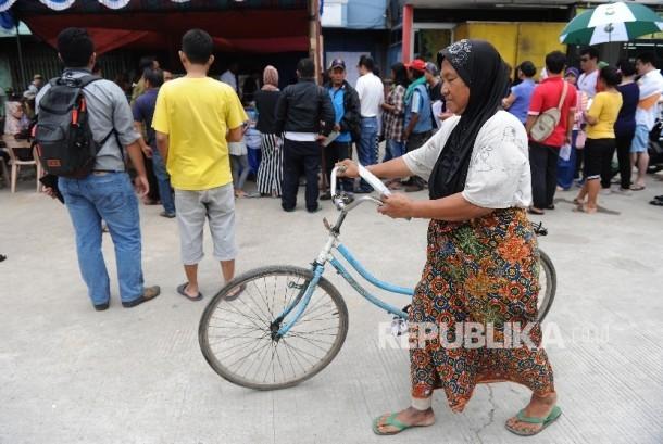 Warga Kampung Aquarium menuntun sepedanya usai mengikuti Pilkada DKI Jakarta di TPS 16, Penjaringan, Jakarta Utara, Rabu (15/2).