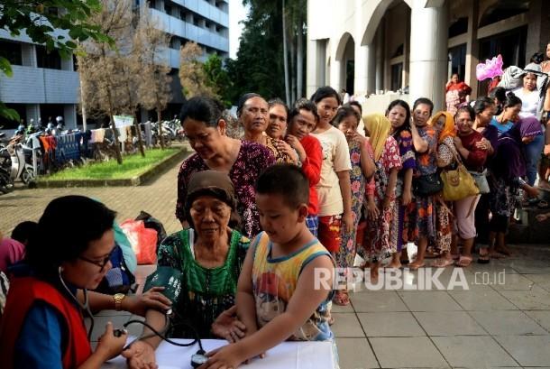 Warga korban banjir mengantri memeriksa kesehatan di lokasi pengungsian di Masjid Univesitas Borobudur, Jakarta,Rabu (22/2).