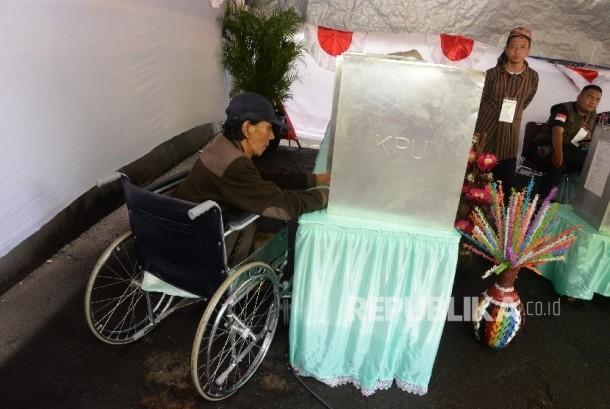 Warga lanjut usia memakai kursi roda menggunakan hak pilihnya dengan dibantu petugas KPPS dalam Pilkada DKI Jakarta di TPS 04 Gambir, Jakarta (15/2).
