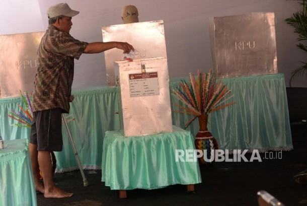 Warga lanjut usia memakai tongkat menggunakan hak pilihnya dengan dibantu petugas KPPS dalam Pilkada DKI Jakarta di TPS 04 Gambir, Jakarta (15/2).