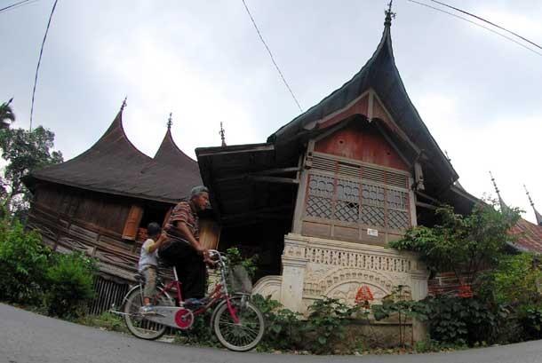 Warga melintas di depan rumah gadang di kampung 1000 rumah gadang di Nagari Koto Baru, Sumbar.  (Ilustrasi)