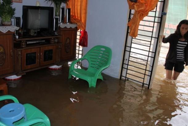Warga melintas didepan rumahnya yang terendam banjir di Pekanbaru, Riau. Derasnya hujan yang mengguyur Pekanbaru sekitarnya, membuat Sungai Sail meluap yang mengakibatkan sedikitnya enam puluh rumah terendam banjir.