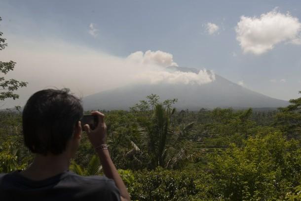 Warga memotret asap yang mulai mengepul dari kawah Gunung Agung dari Pos Pemantauan Desa Rendang, Karangasem, Bali, Selasa (19/9).
