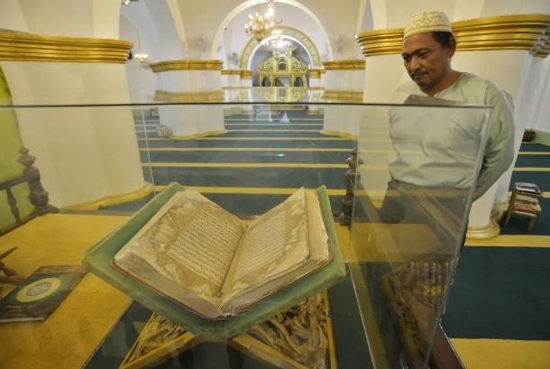Warga mengamati Al-Quran yang dipajang di Masjid Raya Sultan Riau Pulau Penyengat, Kepulauan Riau, Rabu (24/2).