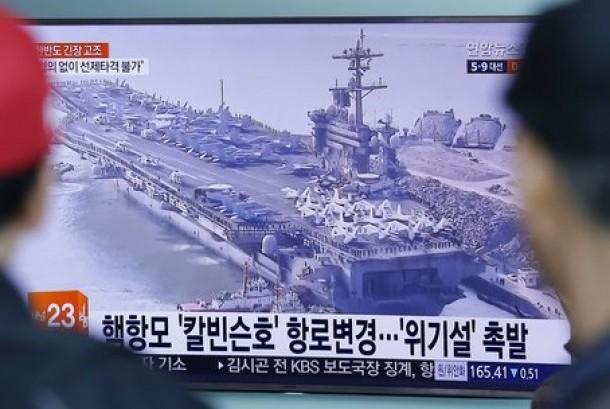 Warga menonton program berita yang menampilkan foto kapal induk AS, USS Carl Vinson di stasiun kereta Seoul, Korea Selatan, 12 April 2017. USS Carl Vinson dalam perjalanan menuju Semenanjung Korea.