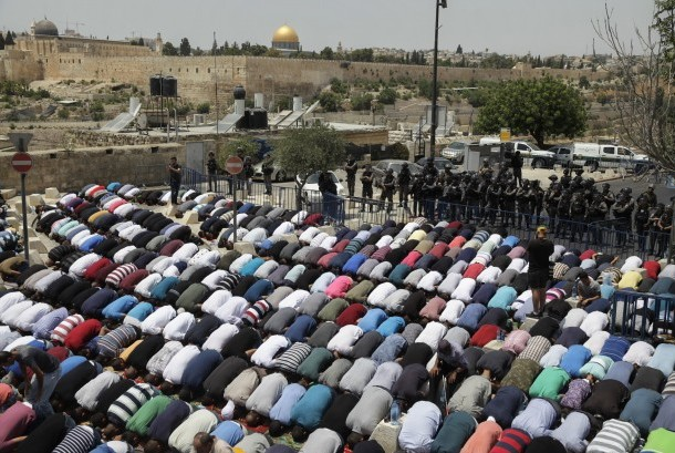 Palestinians perform Friday prayers in the outskirt of Jerusalem Old Town, Friday (July 21).