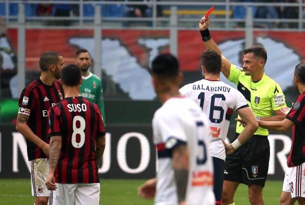 Wasit Piero Giacomelli (kedua dari kanan) memberikan kartu merah kepada kapten AC Milan Leonardo Bonucci (kiri) pada laga Rossoneri kontra Genoa di Stadion San Siro, Ahad (22/10).