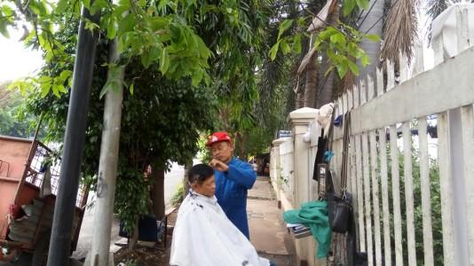 Hasanudin sedang merapikan rambut pelanggannya. Hasan merupakan  satu-satunya tukang cukur DPR yang tersisa di kawasan sekitar Jatinegara. 84fc53d4cb