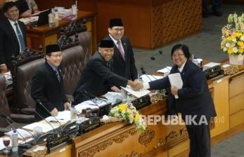 Menteri Lingkungan Hidup dan Kehutanan Siti Nurbaya Bakar (kanan) menyerahkan laporan pengambilan keputusan terhadap Rancangan Undang-Undang tentang konvensi minamata mengenai merkuri kepada pimpinan sidang paripurna DPR Agus Hermanto (kedua kiri), Taufik Kurniawan (kiri) dan Fadli Zon (kanan) di Kompleks Parlemen Senayan, Jakarta, Rabu (13/9).