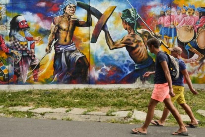 (Ilustrasi) Dua orang wisatawan asing melintas di dekat tembok mural bertemakan atraksi budaya